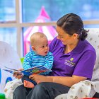 Fonthill Creche Staff Member Reading a Story to a Baby © David Cantwell Photography