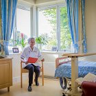 Nurse Sitting with Resident in Bedroom © David Cantwell Photography